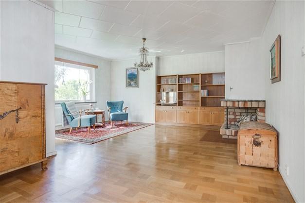 Stort vardagsrum i vinkel med fin stavparkett.