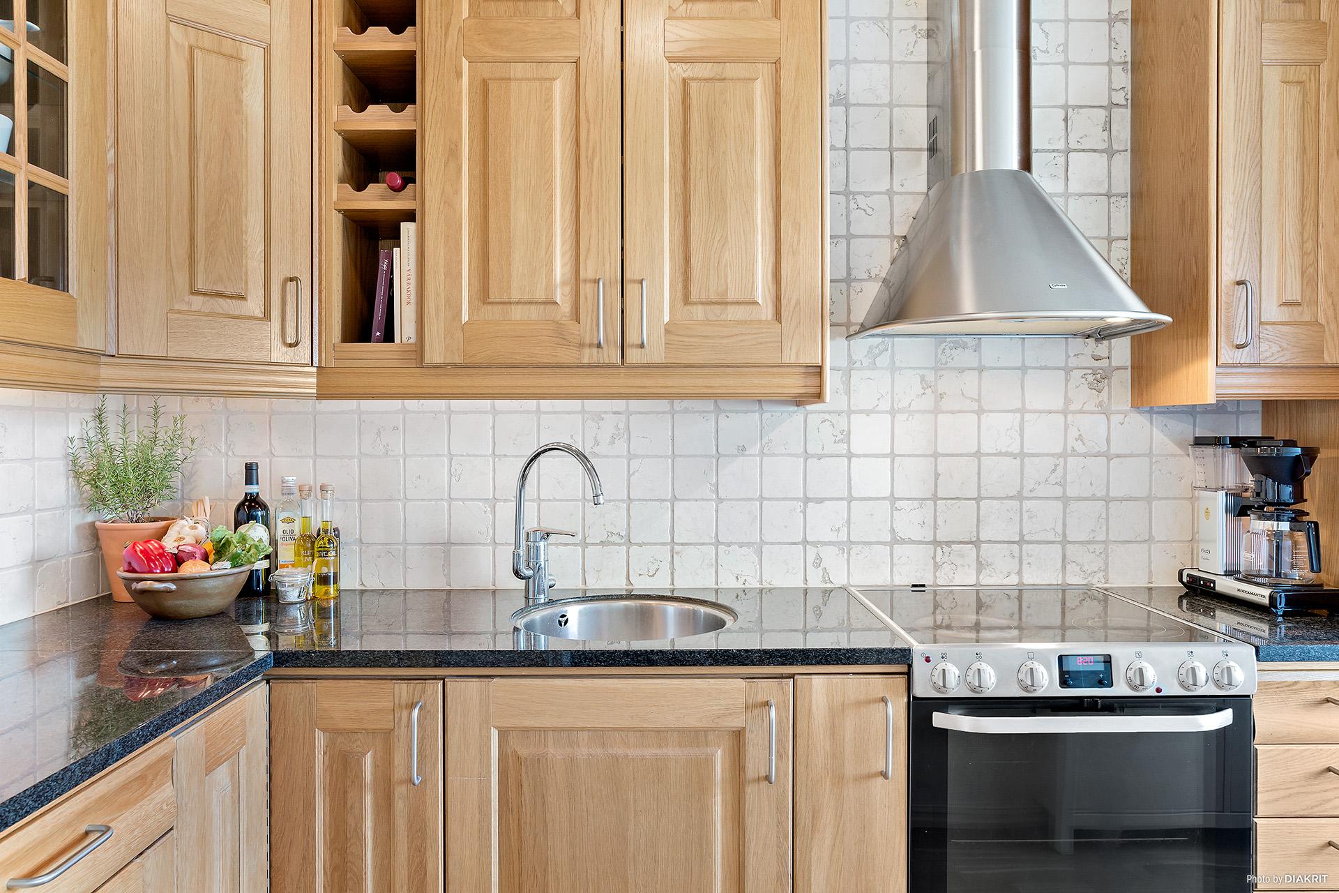 Vitrinskåp, infälld diskho och vinställ är några fina detaljer i köket