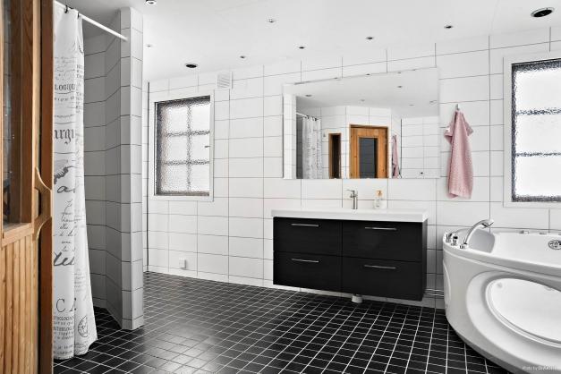 Nyrenoverat badrum med bubbelbadkar, dusch och bastu.