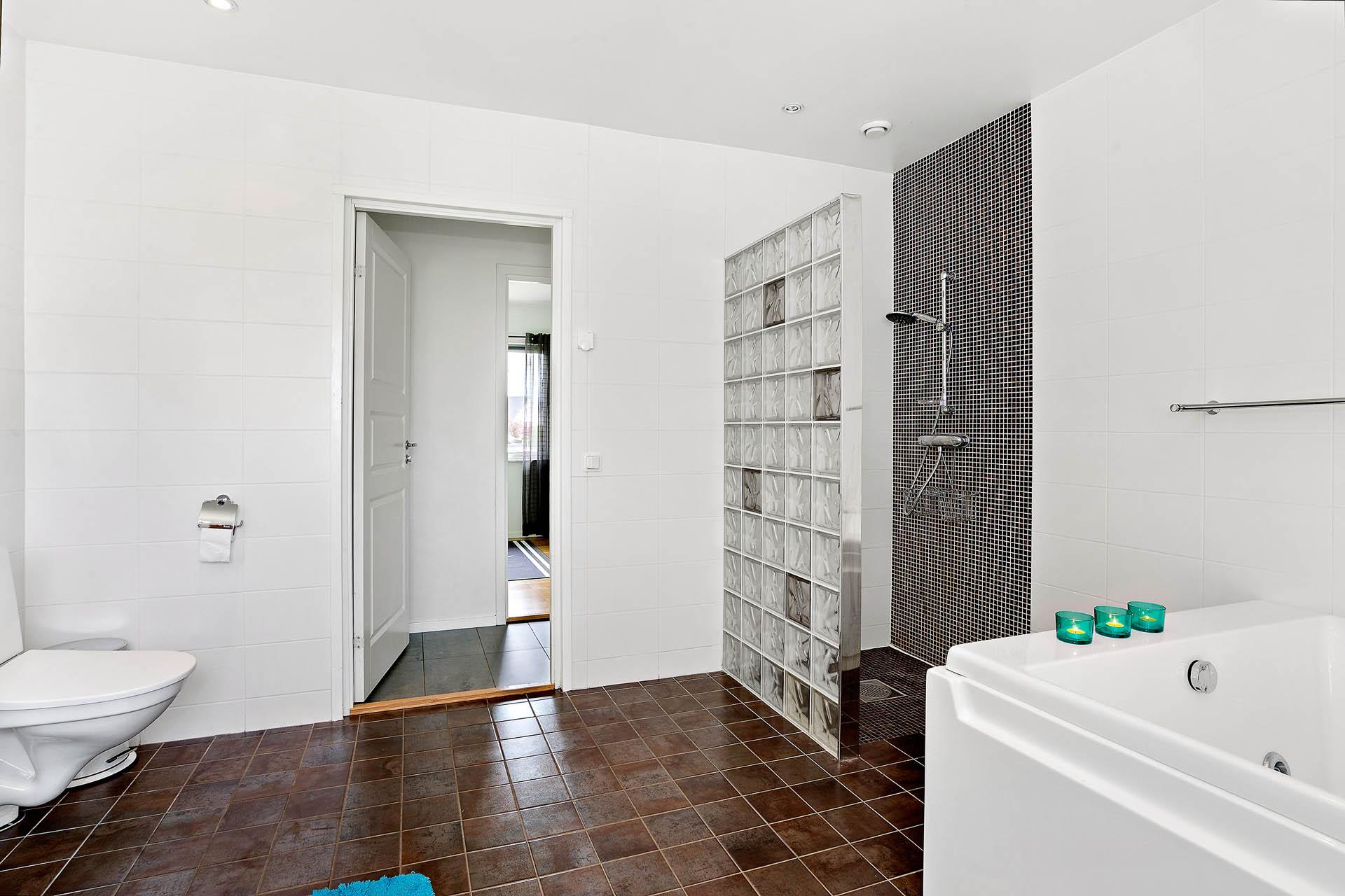 Badrum med bubbelbadkar och dusch