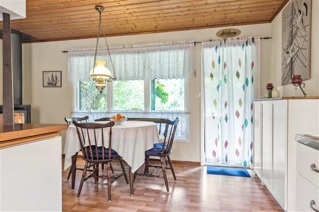 Matplats invid stort fönsterparti samt utgång till trädäckad altan