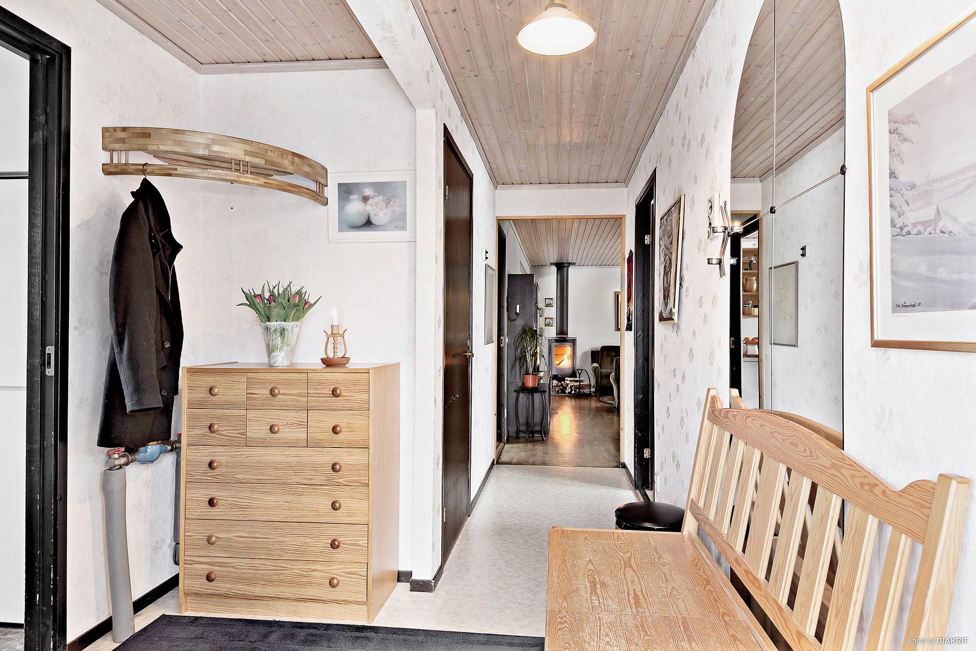 Hall med vy in mot vardagsrum och skymt av tvättstuga till vänster