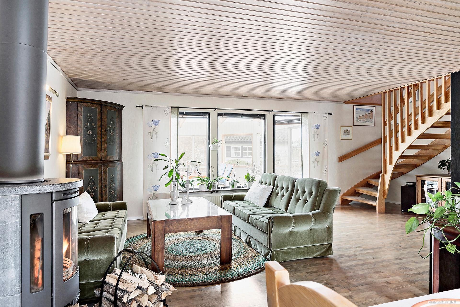 Vardagsrum med kamin och tillgång till uterum