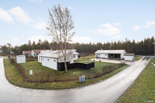 Vy över fastigheten med villa i vinkel och ekonomibyggnad med garage och dubbelgarage