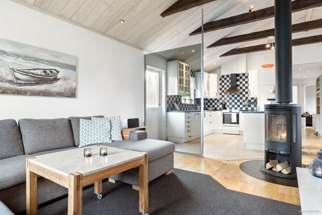 Vardagsrum och kök i öppen modern planlösning samt braskamin