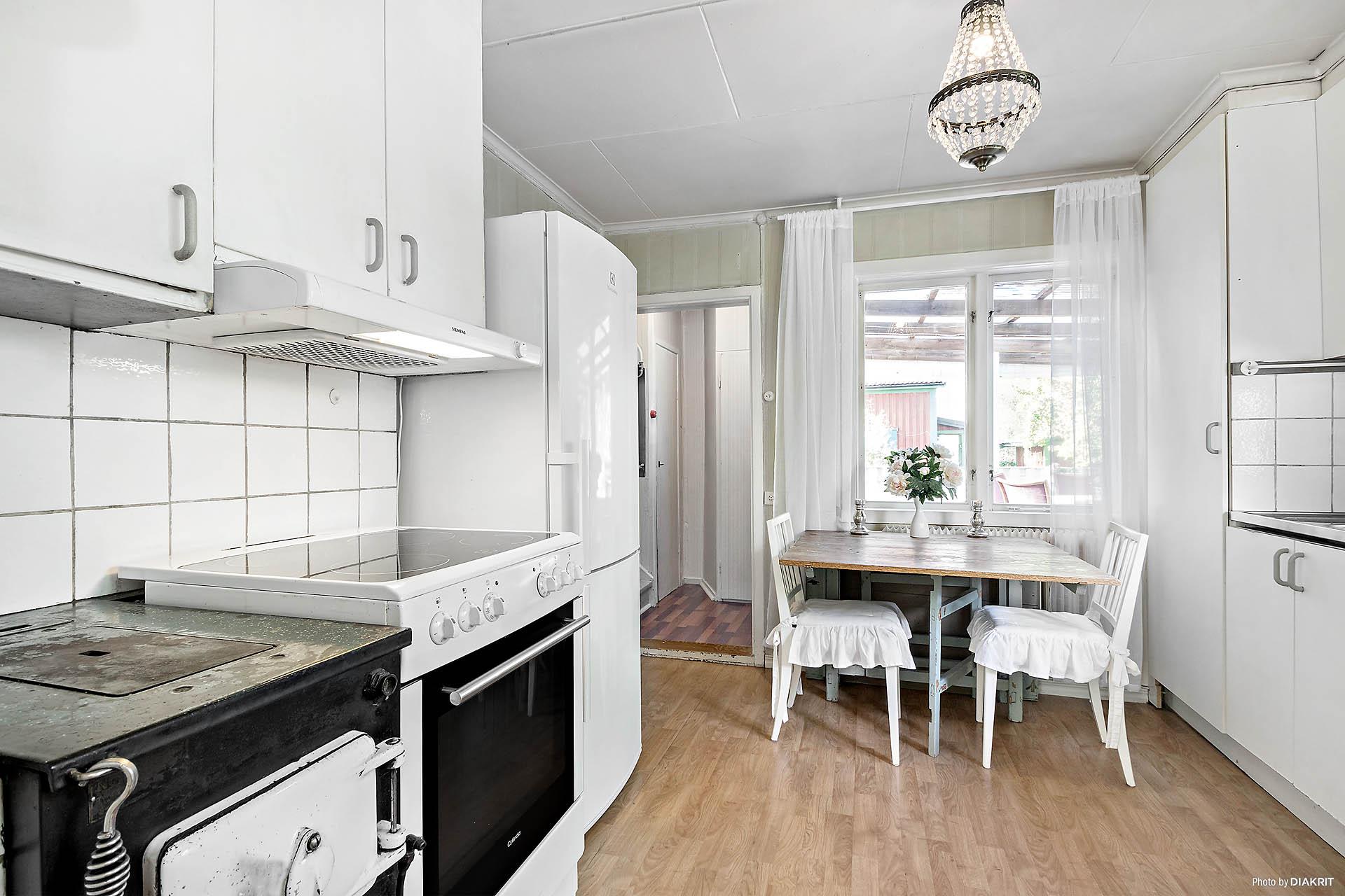 Ljust och trivsamt kök med värmande vedeldning i kökspannan