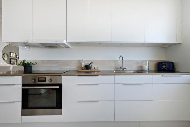 Vitt kök med snyggt stänkskydd