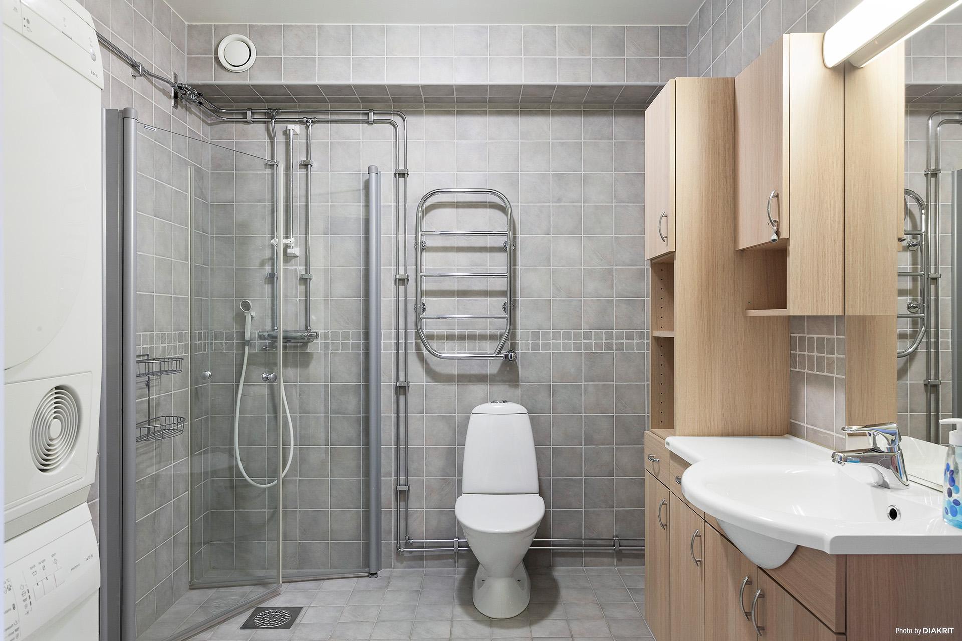 Snyggt helkaklat badrum. Här finns tvättmaskin och torktumlare.