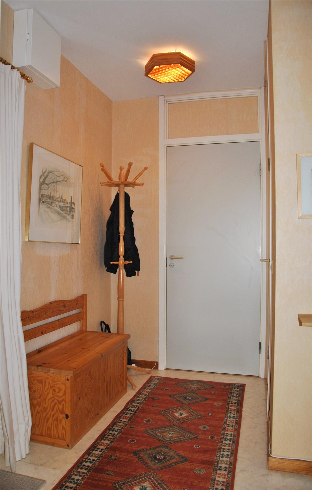 Hall i vinkel med plats för avhängning av ytterkläder.