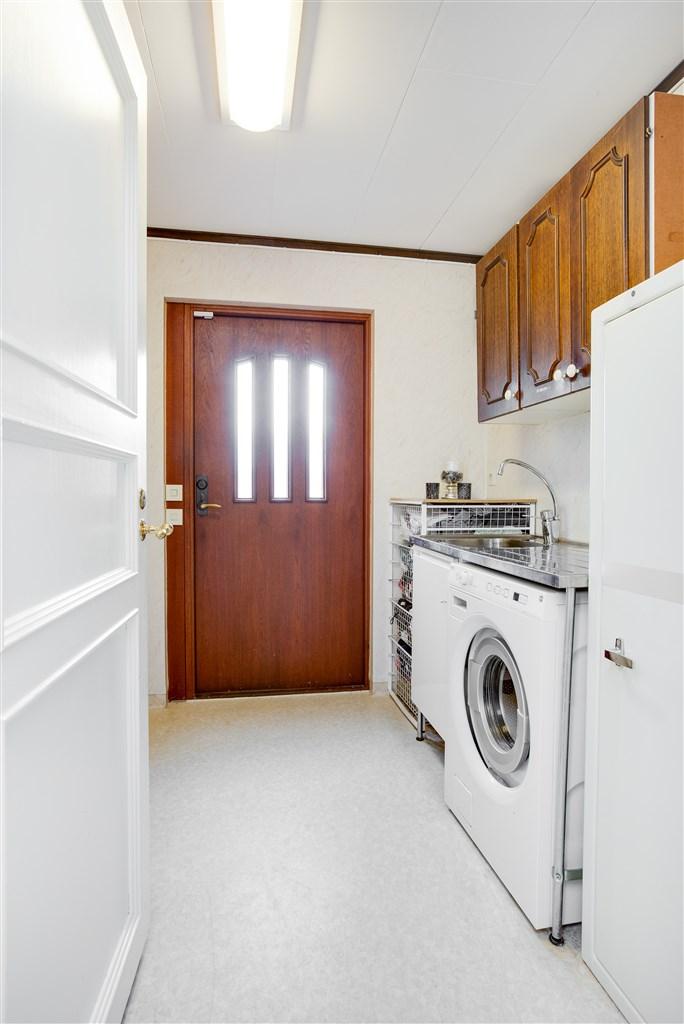 Groventré/tvättstuga med ingång från gaveln av huset.