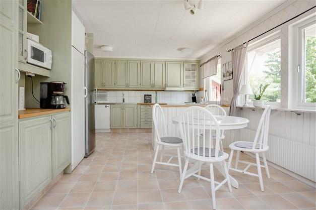 Stort och rymligt kök med ådermålad inredning i skön grön färg.