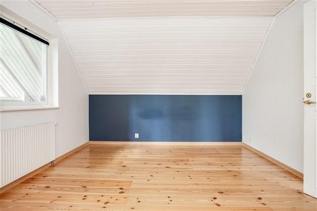 Sovrum 4 med fondvägg i blått. Här finns också luckan till vinden.