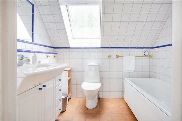 Ljust badrum med takfönster.