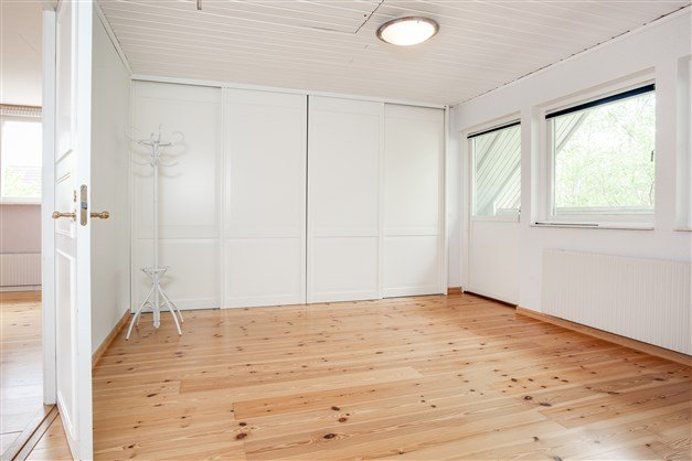 Sovrum 4 med utgång till balkong under tak och stor garderob med skjutdörrar.