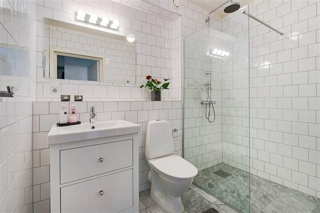 Exklusivt duschrum/wc på entréplan. Marmorgolv,  kaklade väggar, glasvägg mot duschen. Golvvärme