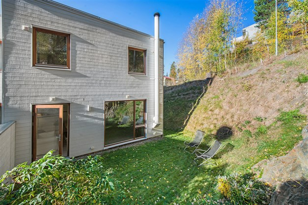 Baksidan av huset med lättskött tomt med gräsmatta.