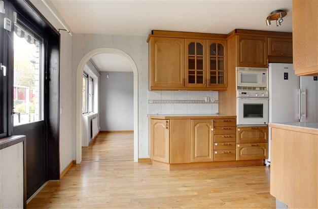 Mellan kök och vardagsrum finns en portal och utgång till uteplats på framsidan.