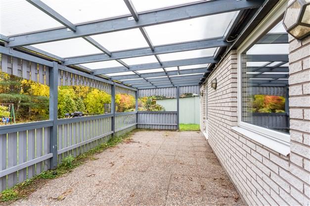 Stor altan med plasttak och trädgårdsplattor.