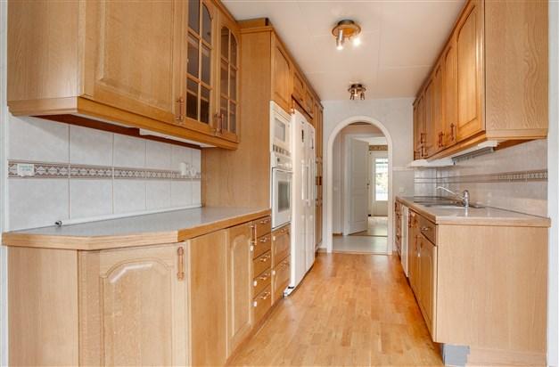 Köket har mycket skåp och arbetsyta.