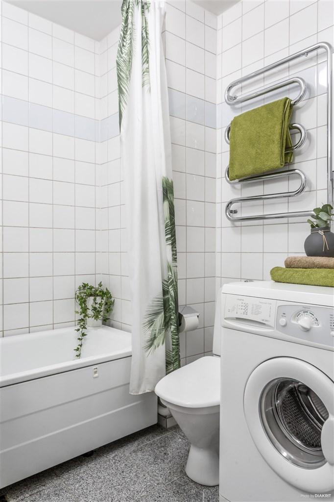Helkaklat badrum med badkar och tvättmaskin.