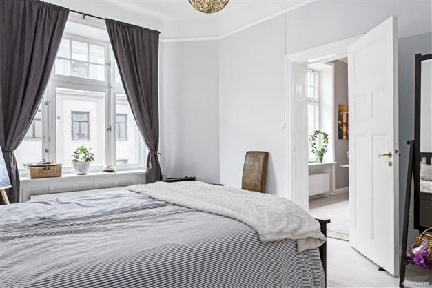 Sovrum och vardagsrum i fil med vackra byggnadsdetaljer.