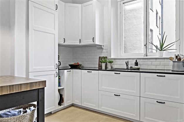 Yteffektivt kök med fönster ovanför diskbänken och utsikt mot innergården.