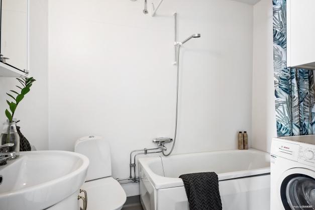 Badrum med badkar och egen tvättmaskin.