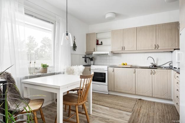 Ljust kök med plats för matbord vid fönster.
