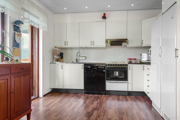 Kök med diskmaskin samt helkyl, helfrys och utgång till den inglasade balkongen
