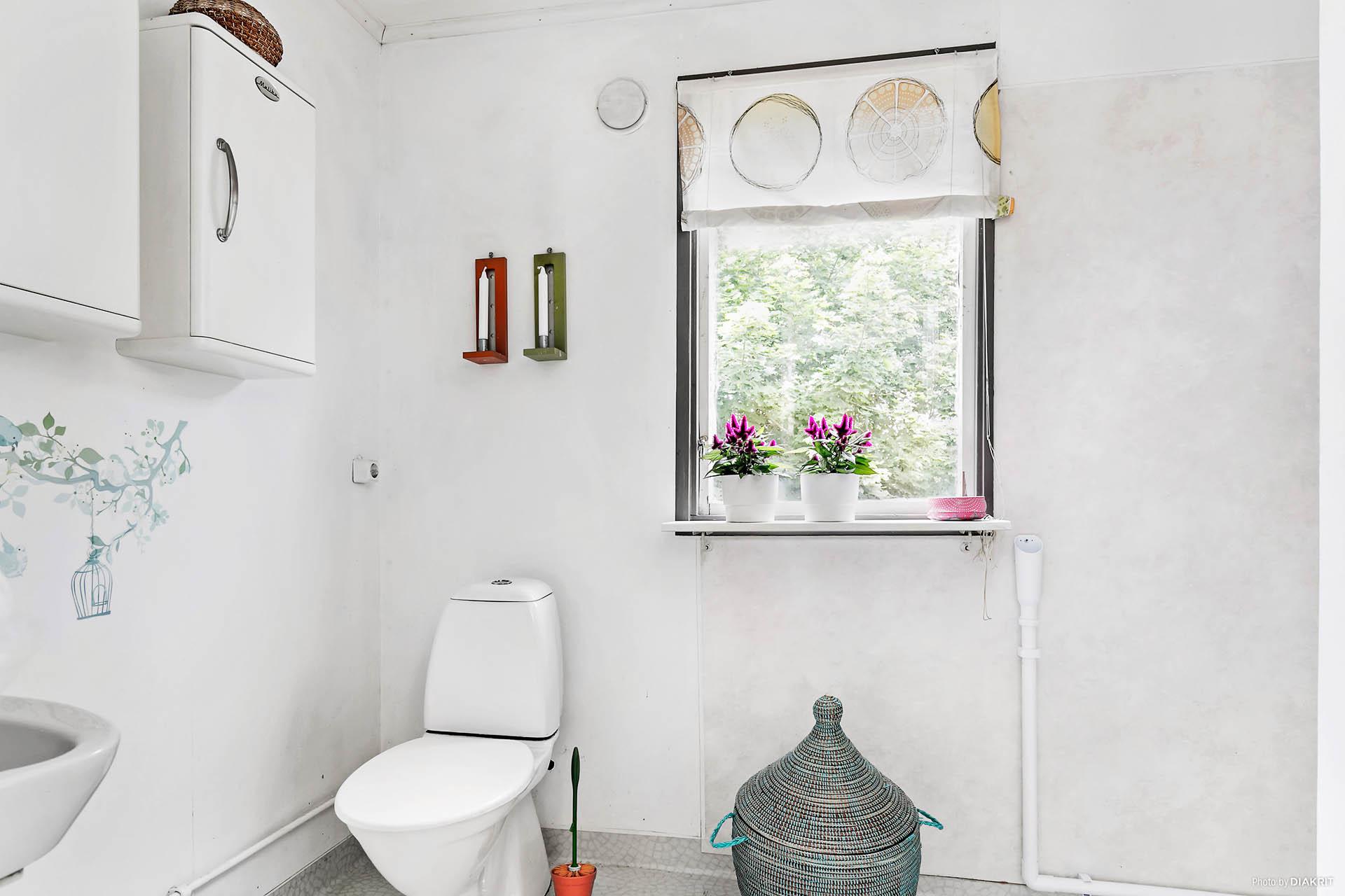 Badrum med toalett, handfat, dusch och förvaring.