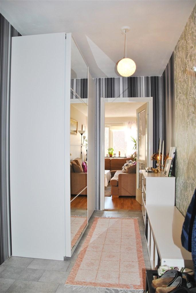 Hallen (mot vardagsrum) med golv av sten och skjutdörrsgarderob med spegelinslag