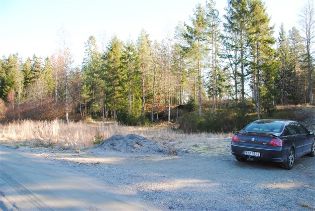 Bilen är parkerad på tomten. Tomtgräns/pinne finns till höger om bilen utanför bilden.
