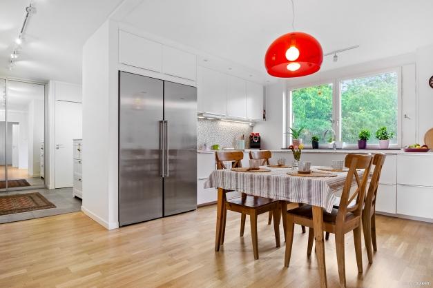 Hall möter kök med stort fönsterparti mot den grönskande innergården