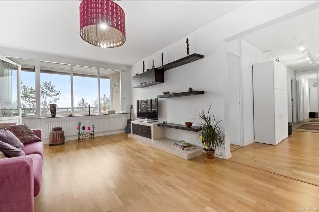 Väl tilltaget vardagsrum med snyggt parkettgolv och vita väggar