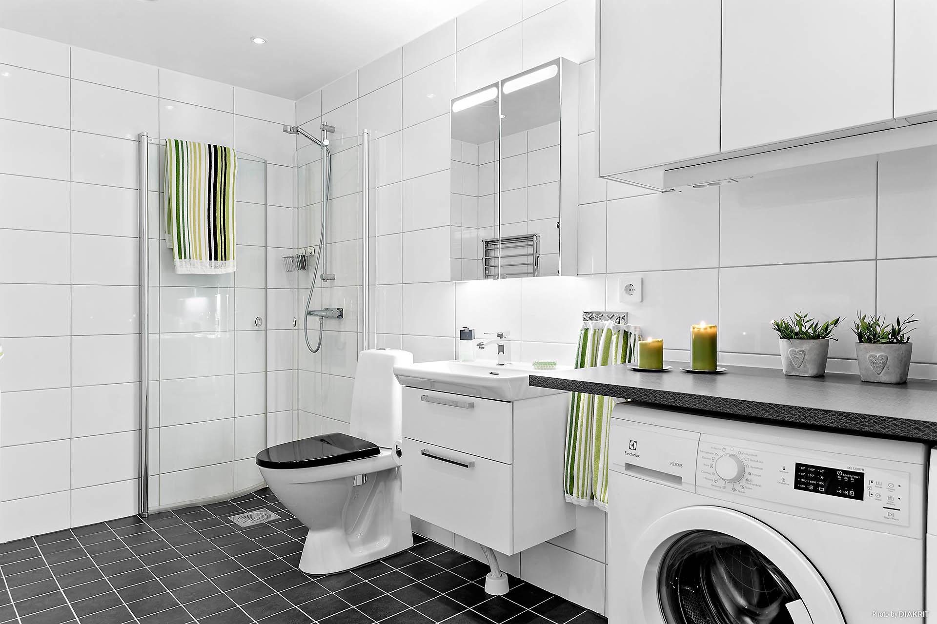 Det stora helkaklade badrummet med tvättmaskin och torktumlare