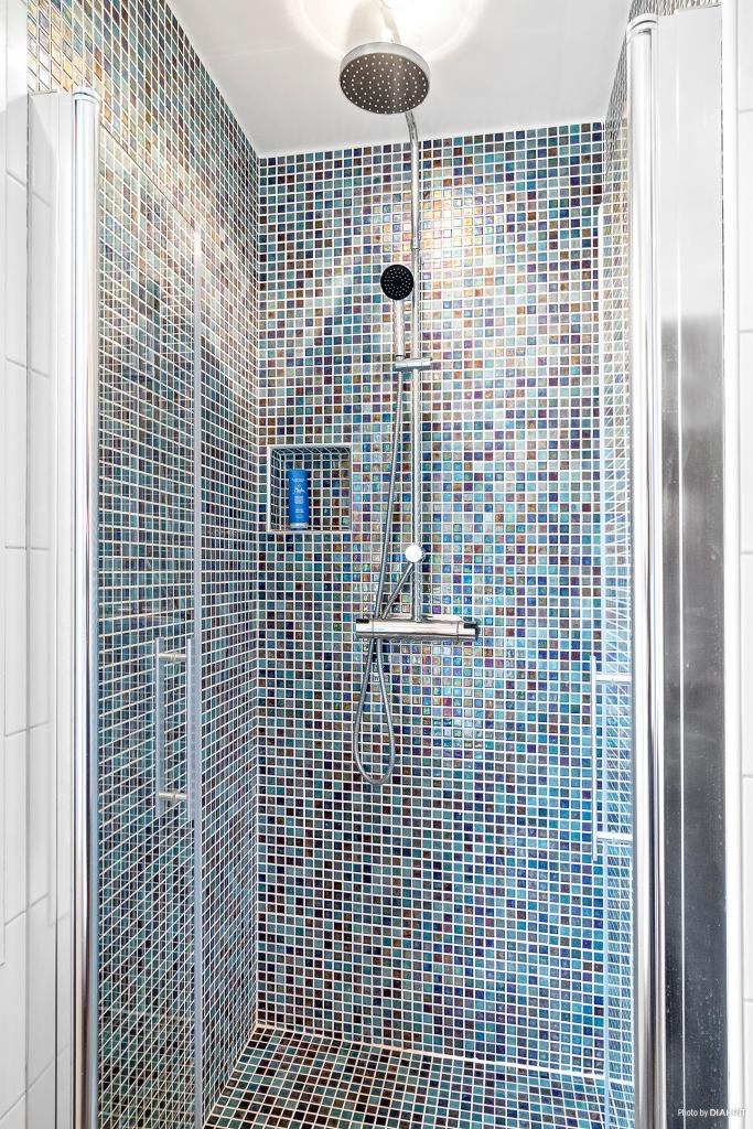 Snyggt mosaikklädd dusch med praktisk nisch