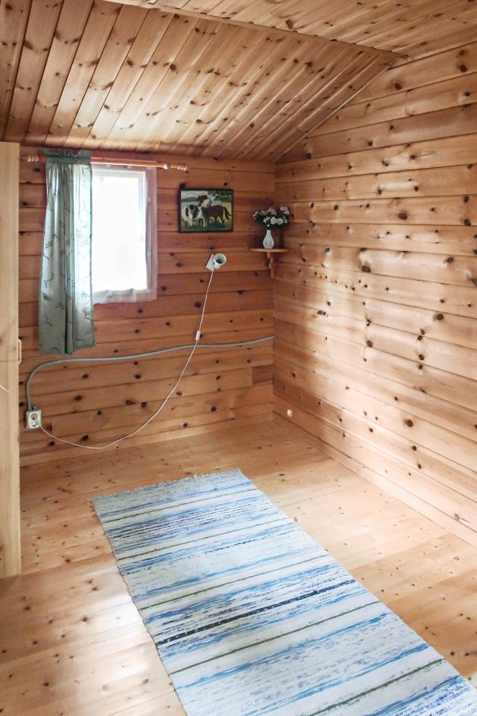 Timrad Jörnstuga: Sovrum med panelväggar och trägolv.