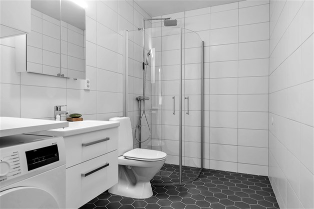Badrummet i lgh 1503. Tillvalsutrustat med mörkt klinkergolv hexagon och vitlackerad handfatskommod med utdragbara lådor.