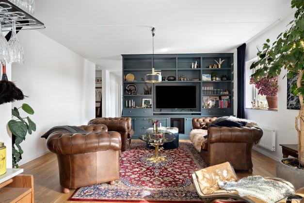 Stort vardagsrum med härligt ljusinsläpp och en fantastisk platsbyggt hyllsystem.