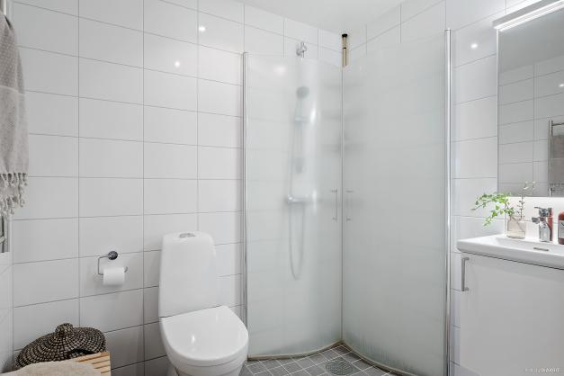 Helkaklad gästtoallet i grå och vita nyanser med dusch, wc och handfat.