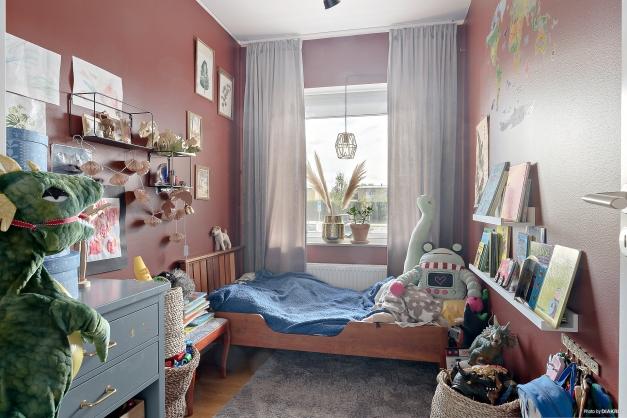 Sovrum 1 med smakfull röd färg med bruna inslag och en garderob.