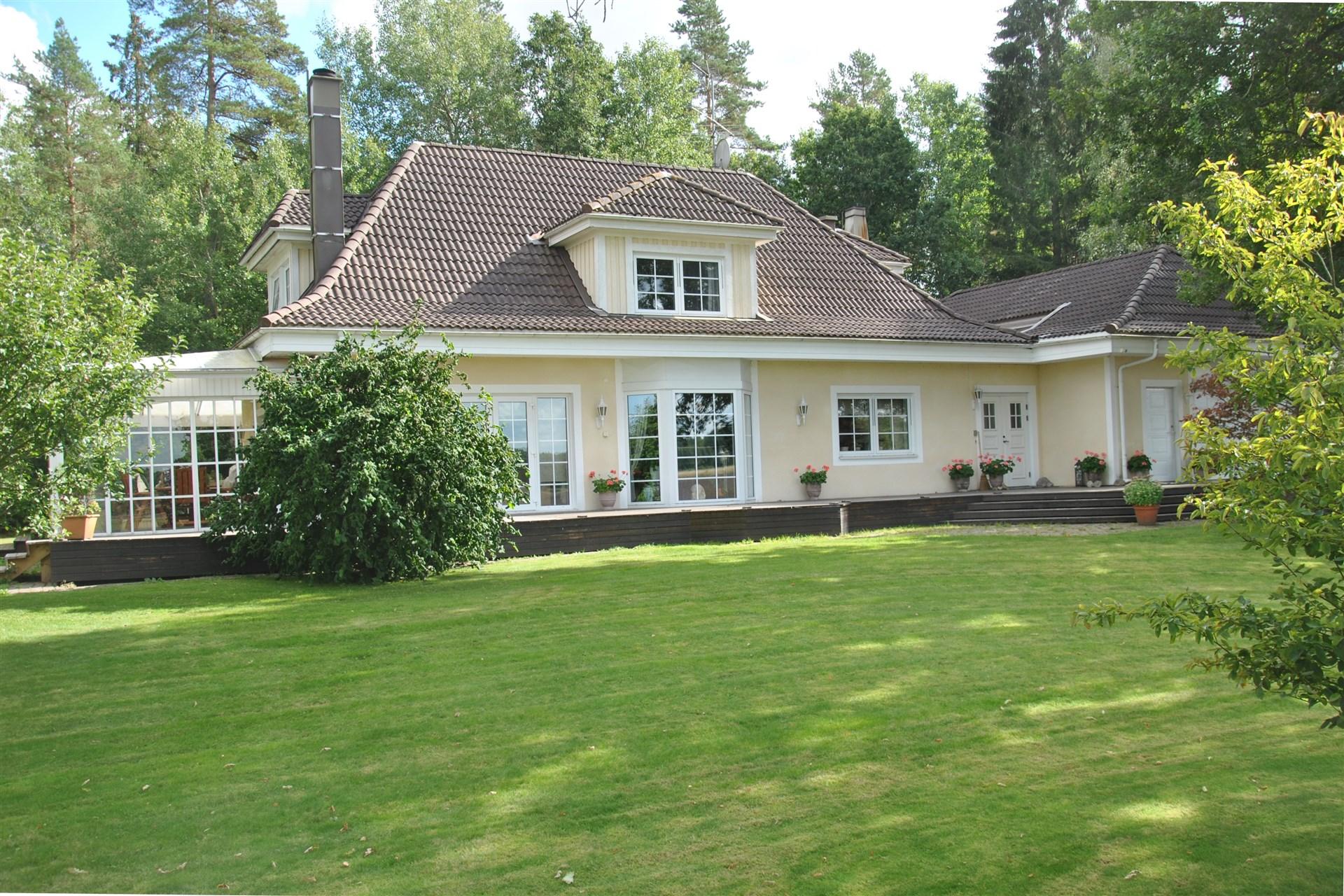 Gediget lösvirkeshus med putsad fasad, valmat tak och integrerat dubbelgarage