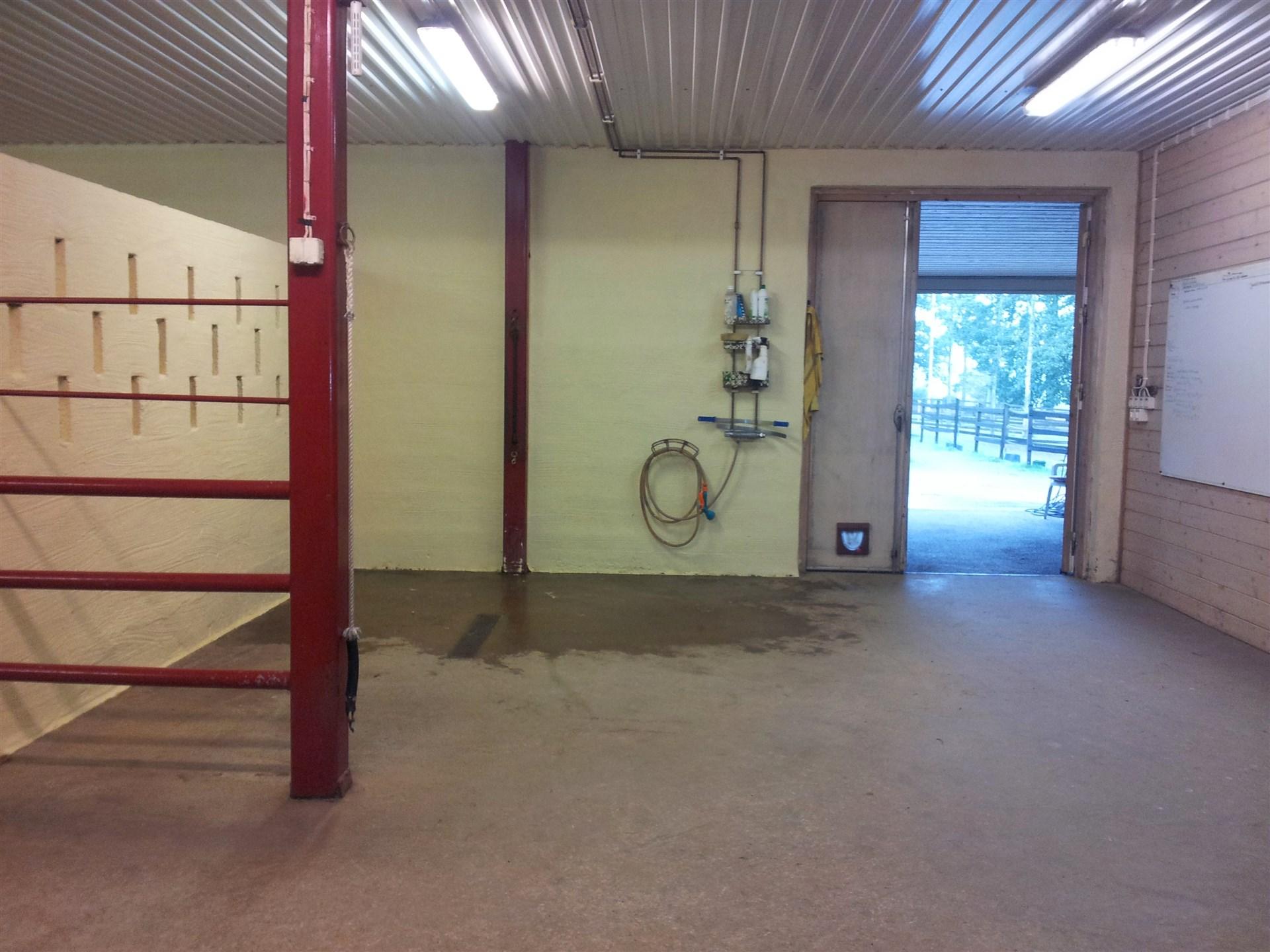 Ingång till stallet med intilliggande spolplatta (säljares bild)