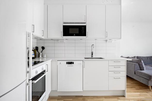 Ljust kök i moderna färger med exklusiv stenskiva.