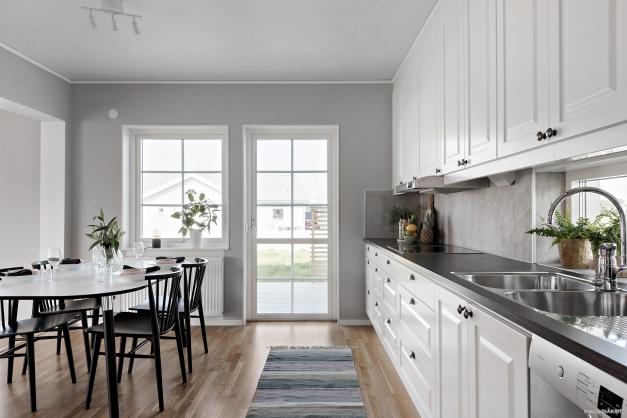 Stilrent kök med intilliggande matplats. Vita luckor harmonierar fint ihop med mörkare bänkskiva och vitt kakel