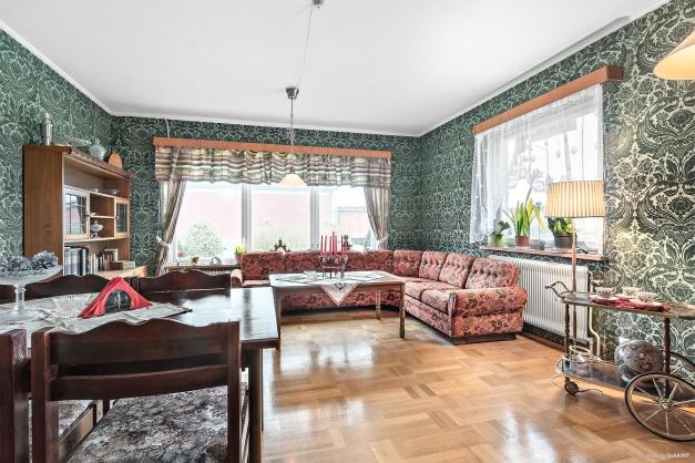 Rymligt vardagsrum med vackert ljusinsläpp. Välvårdad retro tapet i sammet och ekparkett på golv