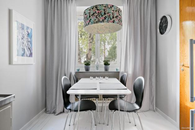 Kök med plats för matbord vid fönster.