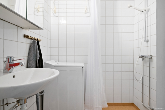 Ljust badrum med delvis kaklade väggar i vitt. Smidigt med egen tvättmaskin.