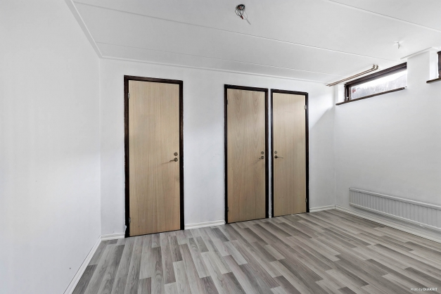 Hall i källarplan med dörrar till två förråd samt toalett