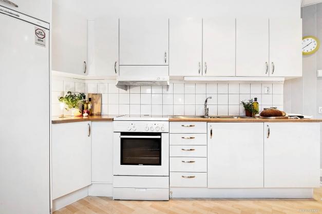 Kök i ljus interiör med stänkskydd i vitt